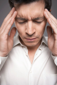 Closeup Of Male Executive With Fingers Pressed To Forehead as if in intense pain from a migraine