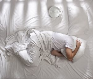 Man under white sheets with pillow on head trying to sleep in bed. A white clock showing seven o'clock in the morning.