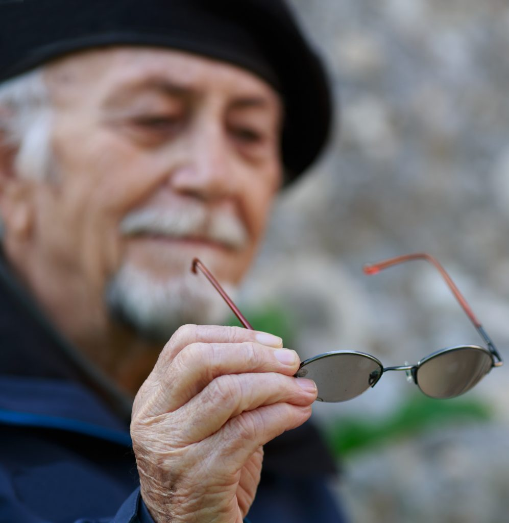 Older man with white hair, wearing a hat, looks at his spectacles as he is trying to hold it with a steady hand.