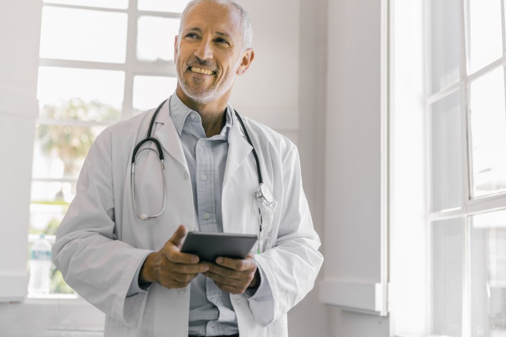 A photo of cheerful male doctor holding digital tablet in clinic. Thoughtful medical professional is wearing lab coat. Mature healthcare practitioner is standing at brightly lit office.